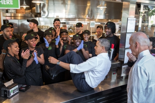 President Barack Obama slides across a counter to pose for photos with staff following lunch at the Dupont Circle Shake Shack in Washington, D.C., May 16, 2014. (Official White House Photo by Pete Souza)