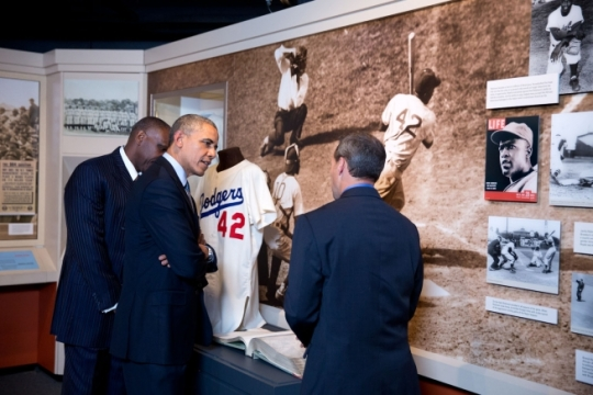 President Barack Obama looks at a jersey worn by Hall of Famer Jackie Robinson, the first African American to break into the Major Leagues, during a tour of the Baseball Hall of Fame in Cooperstown, N.Y., May 22, 2014. Baseball Hall of Fame President Jeff Idelson is at left and Hall of Famer Andre Dawson is at right. (Official White House Photo by Pete Souza)
