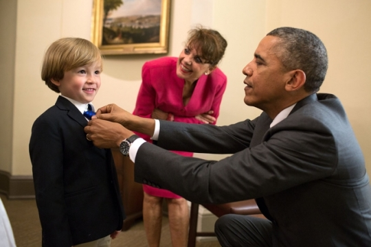 President Barack Obama adjusts the tie of Coast Guard Military Aide Cdr. Scott S. Phy's son outside the Oval Office, June 12, 2014. Cdr. Phy and his family were in the Oval Office for an award citation and departure photos with the President. (Official White House Photo by Pete Souza)