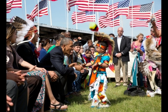 President Barack Obama, with First Lady Michelle Obama, greets a young boy during the Cannon Ball Flag Day Celebration at the Cannon Ball powwow grounds during a visit to the Standing Rock Sioux Tribe Reservation in Cannon Ball, N.D., June 13, 2014. (Official White House Photo by Pete Souza)