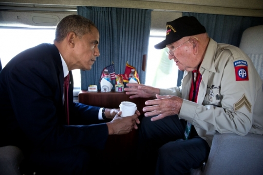 President Barack Obama and WWII veteran Kenneth (Rock) Merritt talk onboard Marine One after departing the 70th French-American Commemoration D-Day Ceremony at the Normandy American Cemetery and Memorial in Colleville-sur-Mer, France, June 6, 2014. (Official White House Photo by Pete Souza)