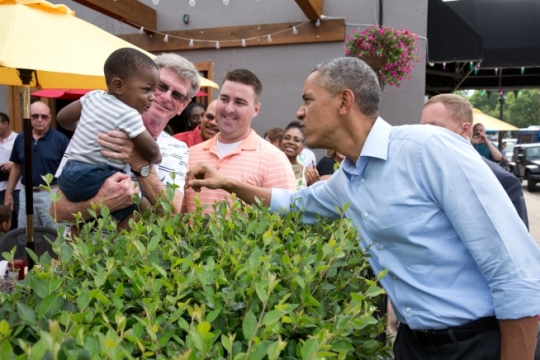 President Barack Obama jokes with a youngster while walking down Grand Avenue in St. Paul, Minn., June 26, 2014. (Official White House Photo by Pete Souza)
