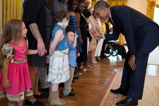President Barack Obama holds up three fingers while talking with three-year-old Holden Fossum and his sisters Ayla, 8, and Alexandria, 4, during a greet with wounded warriors and their families in the East Room of the White House, July 14, 2014. Holden, Ayla, and Alexandria are the children of Staff Sergeant Brendan Fossum and wife Dana of Woodbine, Md. (Official White House Photo by Pete Souza)