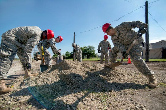 Engineers from the 317th Engineer Company shovel a load of gravel to create a tent pad at the Joliet Training Area in Elwood, Illinois, to prepare the site for a Warrior Training Exercise scheduled for May 2015. The company used this work as an innovative readiness training opportunity to maintain and improve its engineer skills. The Joliet Training Area is the largest local training area run by the 88th Readiness Support Center in the Army Reserve. The 317th Eng. Co. falls under the 416th Theater Engineer Command. (U.S. Army photo by Sgt. 1st Class Michel Sauret)