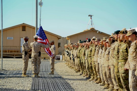 Coalition forces in Regional Command (SouthWest) salute as the United States flag is raised during the 9/11 ceremony aboard Camp Leatherneck, Helmand province, Afghanistan, on Sep 11, 2014. The ceremony was held to commemorate the terrorist acts that occurred on September 11, 2001. (Official U. S. Marine Corps photo by Sgt. Dustin D. March/Released)