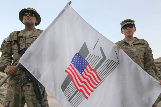 Sgt. Rovin Seosankar, a financial analyst, and Sgt. Jennifer Pineda, the Milpay noncommissioned officer in charge, with the 4th Financial Management Sustainment Detachment, New York National Guard, pose with a 9/11 commemorative flag Sept. 9, 2014, at Kandahar Airfield, Afghanistan. The 4th FMSD will run on Sept. 11 in honor of New Yorkers who responded to the attack on the World Trade Center twin towers. (U.S. Army photo by Staff Sgt. Rich Stowell)