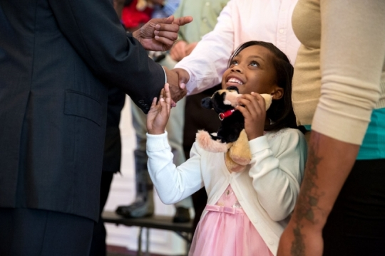 A little girl looks up at President Barack Obama as he talks with wounded warriors and their families in the East Room during their tour of the White House, Sept. 22, 2014. (Official White House Photo by Pete Souza)