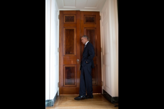 """President Barack Obama listens through a door in the Green Room of the White House as Lilly Jay relates her experience as a sexual assault survivor during the launch of the """"It's On Us"""" campaign, a new public awareness and action campaign designed to prevent sexual assault at colleges and universities, in the East Room, Sept. 19, 2014. (Official White House Photo by Pete Souza)"""