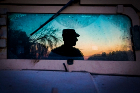"""A soldier from the 36th Infantry Division, Texas Army National Guard observes a section of the Rio Grande River at sunset in support of Operation Strong Safety. The photo was taken using the reflection off the windshield of a M114 """"Humvee"""" at the Texas-Mexico border. (U.S. Army photo by Maj. Randall Stillinger)"""