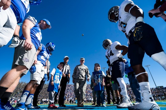 18th Chairman of the Joint Chiefs of Staff Gen. Martin E. Dempsey flips the game coin into the air at the start of the Air Force versus Navy football game at the U.S. Air Force Academy's Falcon Stadium in Colorado Springs, Colorado, Oct. 4, 2014. DoD photo by Army Staff Sgt. Sean K. Harp/Released