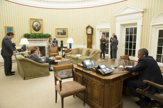 President Barack Obama talks on the phone with Gov. Rick Perry of Texas in the Oval Office with his senior advisors standing by, Oct. 16, 2014. The President spoke to Gov. Perry to make sure Dallas and Texas has the necessary resources if more workers become ill with the Ebola virus. (Official White House Photo by Pete Souza)
