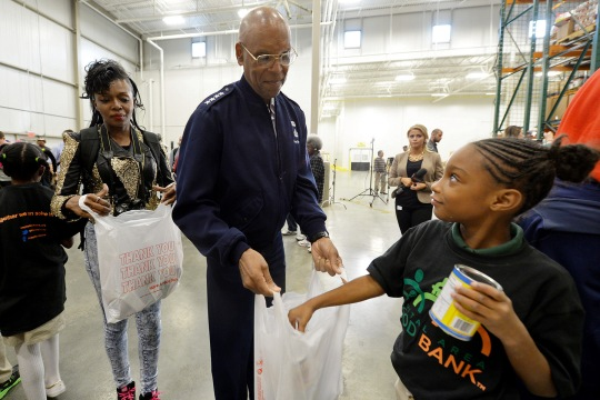General Larry Spencer, Air Force vice chief of staff, holds a food assembly bag during a volunteer effort at the Capital Area Food Bank in Washington, D.C. Oct. 24, 2014. The Department of the Defense and the National Basketball Association have joined forces in an initiative named 'Commitment to Service' to create a culture of service and volunteerism in communities where service members work and live.  (DoD News photo by EJ Hersom)