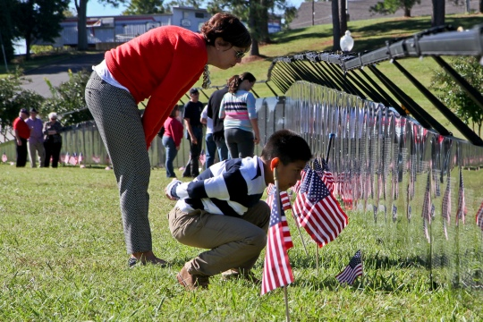 """Mother and child peer at the names inscribed on the traveling """"Wall that Heals"""". Approximately 8,000 people visited the memorial in Fort Mill, S.C. from Oct. 15-19. Eleven service members from Fort Mill died from wounds directly received during the Vietnam conflict."""