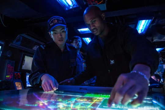 Operations Specialist 2nd Class Keith Reeves, right, assigned to the Arleigh Burke-class guided-missile destroyer USS Mustin (DDG 89), monitors a console with Japan Maritime Self-Defense Force Lt. j.g. Kotaro Kitahara in the ship's combat information center during Exercise Keen Sword 2015. Keen Sword, a joint/bilateral field training exercise involving U.S. military and Japan Self-Defense Force, is designed to increase combat readiness and interoperability of U.S. forces and JSDF. (U.S. Navy photo by Mass Communication Specialist 2nd Class Declan Barnes/Released)