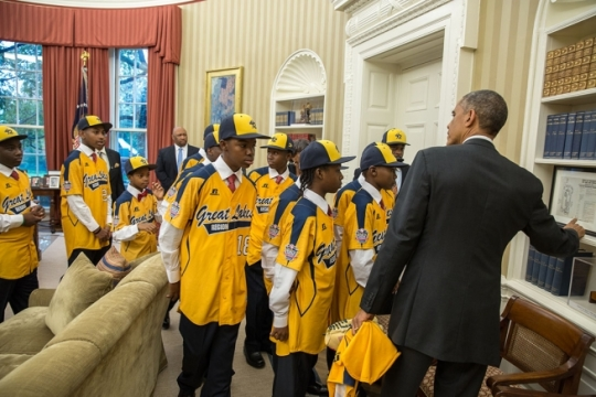 President Barack Obama shows a program for the Martin Luther King Jr. March on Washington to the Jackie Robinson West All Stars during the team's visit to the Oval Office, Nov. 6, 2014. (Official White House Photo by Pete Souza)