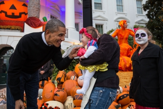President Barack Obama hands treats out to local children and children of military families for trick-or-treat at the South Portico of the White House on Halloween, Oct. 31, 2014. (Official White House Photo by Pete Souza)