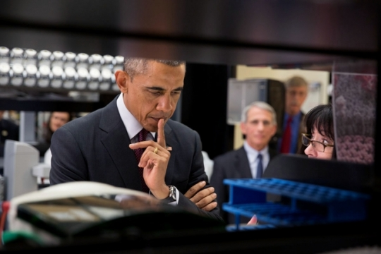 President Barack Obama listens to Dr. Nancy Sullivan, Senior Investigator, Chief Biodefense Research Section explain the investigational Ebola vaccine candidate currently being tested on humans during a lab tour at the Vaccine Research Center at the National Institutes of Health in Bethesda, Maryland, Dec. 2, 2014. Dr. Anthony Fauci, Director, National Institute of Allergy and Infectious Diseases and Dr. Francis Collins, Director, NIH watch in the background. (Official White House Photo by Pete Souza)