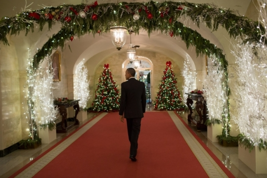 President Barack Obama walks through the Ground Floor Corridor following a White House holiday reception, Dec. 12, 2014. (Official White House Photo by Pete Souza)