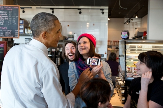 President Barack Obama looks at a selfie with restaurant staff at Charmington's Café in North Baltimore, Md., Jan. 15, 2015. (Official White House Photo by Pete Souza)