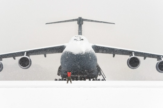 A Team Dover aircraft maintainer stands on the flight line in front of a snow-covered C-5M Super Galaxy Jan. 6, 2015, at Dover Air Force Base, Del. Aircraft maintenance operations continued to keep the mission moving even though 1.4 inches of snow blanketed the flight line and aircraft. (U.S. Air Force photo/Roland Balik)