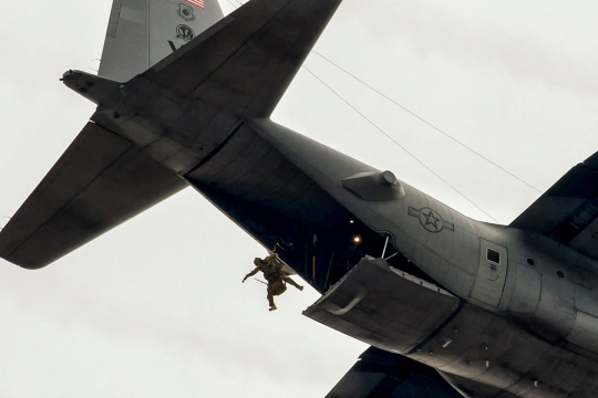 A 31st Rescue Squadron pararescueman jumps out of a 36th Airlift Squadron C-130 Hercules during a training mission over Yokota Air Base, Japan, Jan. 6, 2015. The 36th Airlift Squadron and 31st Rescue Squadron maintain mission readiness for aircrew and pararescuemen. (U.S. Air Force photo by Osakabe Yasuo/Released)