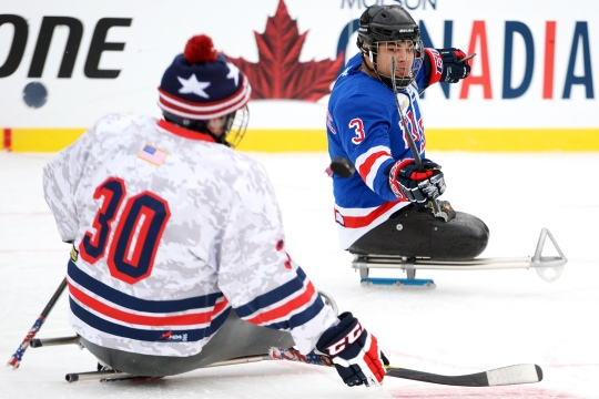 Ralph DeQuebec of the USA Warriors sled hockey team flips a puck past a teammate while playing on the National Hockey League's Winter Classic 2015 outdoor ice at Nationals Park in Washington, D.C., Jan 2, 2015. The NHL honored the wounded veterans hockey club by giving them exclusive access to their teams and facilities for three days during their biggest regular season event of the year. (DoD News photo by EJ Hersom)