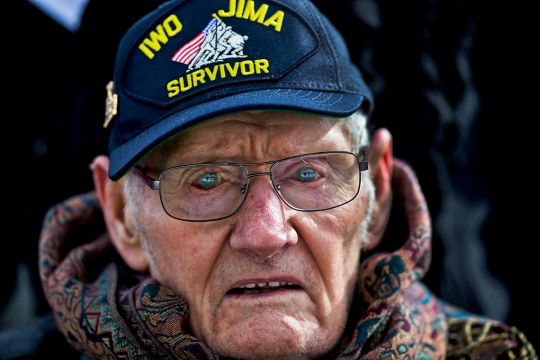 "Lloyd Ford, a Marine veteran of World War II, observes a wreath laying ceremony at the Marine Corps War Memorial in Washington. The Ceremony commemorated the 70th anniversary of the battle for Iwo Jima. ""When we first landed, we got bombarded. This one guy was praying because he had been a lady's man. You start praying at a time like that."" (U.S. Marine Corps photo by Cpl. Clayton Filipowicz/Released)"