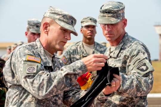 U.S. Army Maj. Gen. Gary J. Volesky, right, commander of Joint Forces Command United Assistance and the 101st Airborne Division, and U.S. Army Command Sgt. Maj. Gregory Nowak, left, senior enlisted advisor for the command and division, case their unit colors during a ceremony at the Barclay Training Center in Monrovia, Liberia, Feb. 26, 2015.
