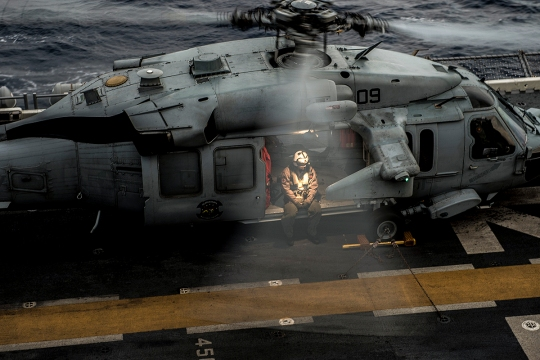150324-N-UF697-009 EAST CHINA SEA (March 24, 2015) A Naval Aircrewman awaits takeoff on an MH-60S Seahawk helicopter, assigned to Helicopter Sea Combat Squadron (HSC) 25, aboard the forward-deployed amphibious assault ship USS Bonhomme Richard (LHD 6). Bonhomme Richard is the lead ship of the Bonhomme Richard Amphibious Ready Group (ARG) and, along with the embarked 31st Marine Expeditionary Unit (MEU), is currently underway in the 7th Fleet Area of Operations. (U.S. Navy photo by Mass Communication Specialist 3rd Class Kevin V. Cunningham/Released)
