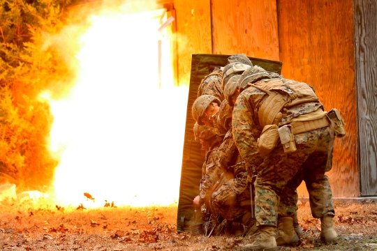 Marines with Mobility Assault Company, 2nd Combat Engineer Battalion, 2nd Marine Division stand behind a blast blanket as detonation cord ignites, blowing the door in and giving them a clear passage to breach the building during an urban breaching course, aboard Camp Lejeune, N.C., March 3, 2015. For each breach, the Marines would stack up behind a blast blanket, which allows them to stand closer to the blast by protecting them from shrapnel and debris. (U.S. Marine Corps photo by Cpl. Justin T. Updegraff)