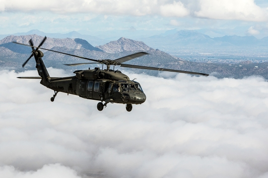An Arizona Army National Guard UH-60 Black Hawk helicopter with 2-285th Assualt Helicopter Battalion in Phoenix soars over a low layer of clouds during a flight to the Western Army Aviation Training site in Marana, Ariz. March 4, 2015. (U.S. Army National Guard photo by Staff Sgt. Brian A. Barbour)