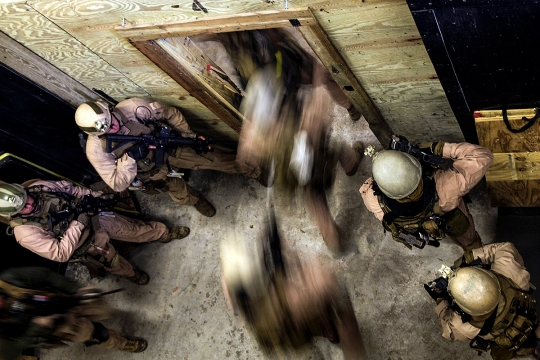 A fire team with 2nd Force Reconnaissance Detachment 6 enters a room after throwing in a flash bang during a close-quarters tactics training event at Expeditionary Operations Training Group compound at Stone Bay aboard Marine Corps Base Camp Lejeune, N.C., March 6, 2015. More than 35 Marines conducted the training during a pre-deployment training package provided by EOTG instructors.