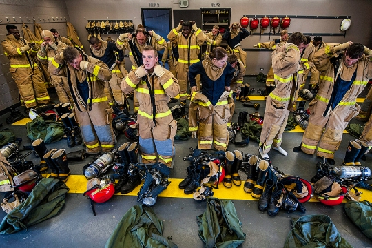 150317-N-IU636-581 PEARL HARBOR (March 18, 2015) Sailors don fire protection equipment in preparation of a general shipboard firefighting training evolution at the Surface Warfare Officer's School (SWOS) on Joint Base Pearl Harbor-Hickam. The training allowed students to practice proper hose handling procedures, fire fighting maneuvers, teamwork and nozzle man relieving procedures. (U.S. Navy photo by Mass Communication Specialist 2nd Class Johans Chavarro/Released)