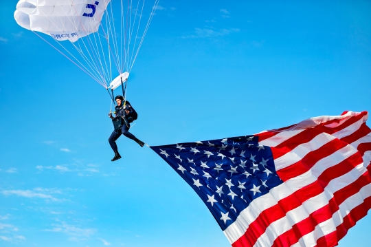Cadet 1st Class Josh Burres, 98th Flying Training Squadron Wings of Blue parachutist, a Greensboro, N.C., native, flies the U.S. flag during an aerial demonstration for the opening ceremonies of the Air Force Wounded Warrior (AFW2) 2015 Trials on Nellis Air Force Base, Feb. 27. The AFW2 Trials are an adaptive sports event designed to promote the mental and physical well-being of seriously ill and injured military members and veterans. More than 105 wounded, ill or injured service men and women from around the country will compete for a spot on the 2015 U.S. Air Force Wounded Warrior Team, which will represent the Air Force at the 2015 Warrior Games held in Colorado Springs, Colo., in the fall. (U.S. Air Force photo/Senior Airman Jordan Castelan)