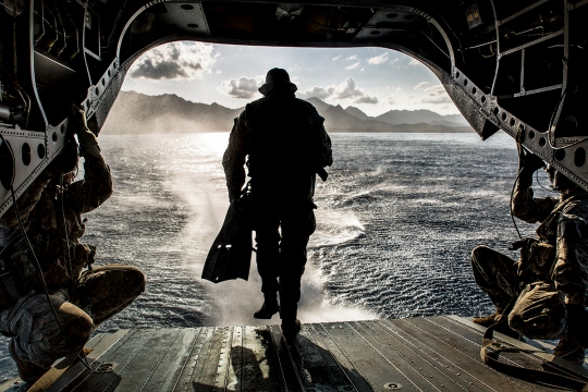 A soldier with Operational Detachment Alpha 1215, 1st Special Forces Group, Joint Base Lewis-McChord, runs off the back of a CH-47F Chinook helicopter while conducting a simulated combat dive mission in the water off of Marine Corps Training Area Bellows, March 16, 2015. The helicopter hovered the ocean and allowed the soldiers to conduct a boat movement leading to reconnaissance of the beach and a raid in the training facility at Bellows. (U.S. Marine Corps photo by Lance Cpl. Brittney Vella/Released)