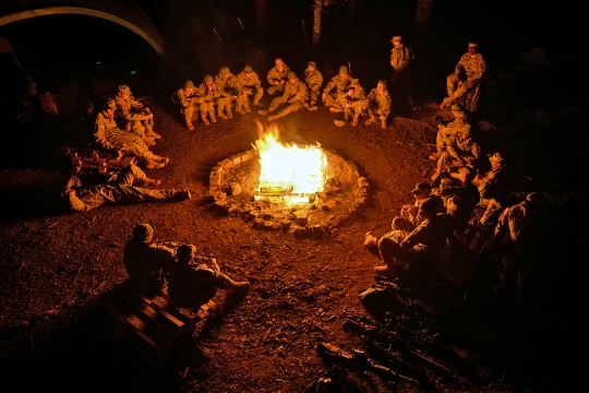 "After a full day of training, U.S. Soldiers assigned to 554th Military Police Company enjoy the warmth of a camp fire before winding down for the night. This was a typical evening during the 96-hour Field Training Exercise, FTX, called ""Operation Mandalorian."" The exercise consisted of various scenarios including simulated terrorist attacks and medical response procedures. This FTX was conducted in the Local Training Area, Boeblingen, Germany, from March 23-26, 2015. (U.S. Army photo by Visual Information Specialist Jason Johnston/Released)"