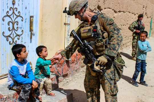 A U.S. Marine shakes hands with an Afghan child while on patrol near Bagram Airfield, Afghanistan, April 6, 2015. The Marine is assigned to the Georgian Deployment Program.