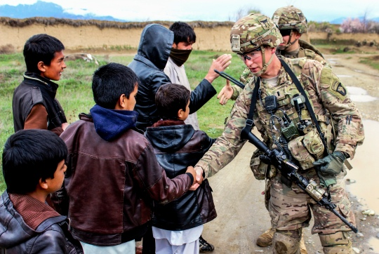 U.S. soldiers shake hands with Afghan children while patrolling through a village near Bagram Airfield, Afghanistan, March 24, 2015. The soldiers are assigned to the 101st Airborne Division's 3rd Battalion, 187th Infantry.