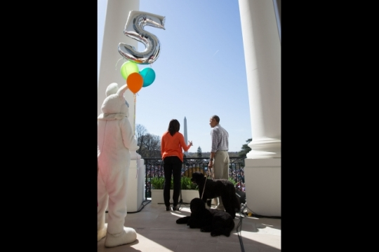 "First Lady Michelle Obama, with President Barack Obama and family pets Sunny and Bo, delivers remarks on the 5th anniversary of the ""Let's Move!"" initiative, and #GimmeFive, on the Blue Room Balcony during the annual Easter Egg Roll on the South Lawn of the White House, April 6, 2015. (Official White House Photo by Pete Souza)"