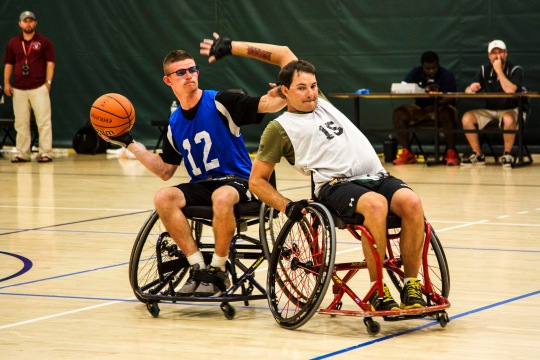 U.S. Army veteran Spc. Jason Blair, Waco, Texas, tries to pass around his defender during the bronze medal wheelchair basketball game during the 2015 Army Trials at Soto Physical Fitness Center, Fort Bliss, Texas, March 31. Approximately 80 wounded, ill and injured Soldiers and veterans are at Fort Bliss to train and compete in a series of athletic events including archery, cycling, shooting, sitting volleyball, swimming, track and field and wheelchair basketball. Army Trials, March 29-April 2, are conducted by the Army Warrior Transition Command and hosted by Fort Bliss. Army Trials help determine who will get a spot on the Department of Defense Warrior Games 2015 Army Team in June at Marine Corps Base Quantico, Va. (U.S. Army photo by Spc. Ambraea Johnson/Released)