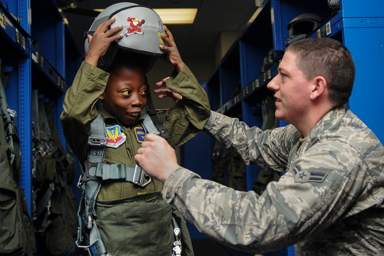 "Airman 1st Class Luke Locken, 4th Operations Support Squadron aircrew flight equipment technician, fits Jeremiah Seaberry, 334th Fighter Squadron pilot for a day, with flight gear during a 4th Fighter Wing Pilot for a Day event, April 3, 2015, at Seymour Johnson Air Force Base, North Carolina. PFAD organizers chose the call sign ""Swoosh"" for Jeremiah as an allusion to his admiration for his favorite basketball player, Lebron James. (U.S. Air Force photo/Senior Airman Ashley J. Thum)"
