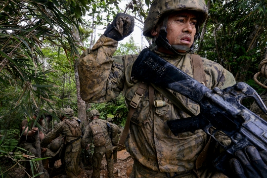 50424-N-SD120-065 OKINAWA, Japan (April 24, 2015) Utilitiesman 2nd Class Elmer Agonias, a Seabee assigned to Naval Mobile Construction Battalion (NMCB) 5,  secures the rear of his patrol while the other Seabees carry a simulated injured team member on an improvised stretcher down a steep hill at Jungle Warfare Training Center in Okinawa. More than 60 Seabees from NMCB 5 attended the week long course taught by Marine instructors. The course is designed to prepare Marines and joint forces for the rigors of combat in a dense jungle environment. NMCB 5 is currently deployed to Japan and several countries in the Pacific area of operations conducting construction operations and humanitarian assistance projects. (U.S. Navy photo by Mass Communication Specialist 1st Class John P. Curtis/Released)