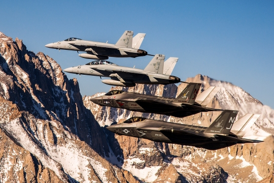 150414-N-SS390-002  LEMOORE, Calif. (April 14, 2015) Two F-35C Lightning II aircraft fly in formation over the Sierra Nevada mountain range with to two F/A-18E/F Super Hornets from Naval Air Station (NAS) Lemoore. The flight is part of a six-day visit by the Grim Reapers of Strike Fighter Squadron (VFA) 101 to NAS Lemoore, the future basing site for the F-35C. The F-35C will complement the capabilities of the F/A-18E/F Super Hornet, which currently serves as the Navy's premier strike fighter. (U.S. Navy photo by Lt. Cmdr. Darin Russell/Released)