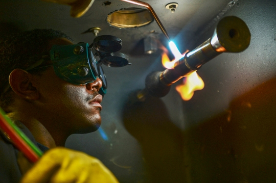 150414-N-KU391-093 U.S 5TH FLEET AREA OF OPERATIONS (April 14, 2015) A Sailor welds metal in the pipe shop aboard the Nimitz-class aircraft carrier USS Theodore Roosevelt (CVN 71). Theodore Roosevelt is deployed in the U.S. 5th Fleet area of responsibility supporting Operation Inherent Resolve, strike operations in Iraq and Syria as directed, maritime security operations and theater security cooperation efforts in the region. (U.S. Navy photo by Mass Communication Specialist 3rd Class Josh Petrosino/Released)