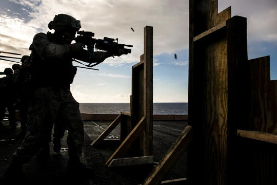 A U.S. Marine with the 15th Marine Expeditionary Unit's Maritime Raid Force shoots at his target on the flight deck of the USS Essex (LHD 2) at sea in the Pacific Ocean, May 28, 2015. These Marines were executing drills that simulate entering a room and immediately seeing a target. (U.S. Marine Corps photo by Cpl. Anna Albrecht/ Released)