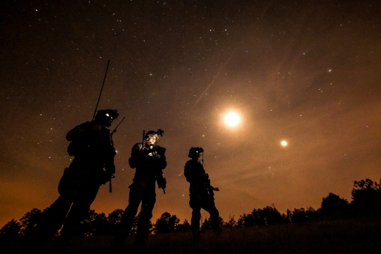 U.S. Air Force combat controllers, 21st Special Tactics Squadron, observe an AC-130 Gunship conduct a live-fire mission during Emerald Warrior at Camp Shelby, Miss., April 22, 2015. Emerald Warrior 2015 is the Department of Defense's only irregular warfare exercise, allowing joint and combined partners to train together and prepare for real world contingency operations. (U.S. Air Force photo by Staff Sgt. Jonathan Snyder/Released)