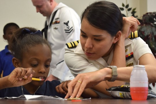 150428-N-VN372-059  SHREVEPORT, La. (April 29, 2015)  Lt. Cmdr. Maura Thompson, assigned to the ballistic-missile submarine USS Louisiana (SSBN 743), helps a child from Volunteers of America's after school program complete homework during the Bossier City, Shreveport Navy Week. Navy Weeks focus a variety of assets, equipment and personnel on a single city for a week-long series of engagements designed to bring America's Navy closer to the people it protects, in cities that don't have a large naval presence. (U.S. Navy photo by Mass Communication Specialist 1st Class Chris Fahey/Released)