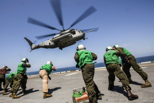 U.S. Marines brace for the rotor wash of a CH-53 Super Stallion while conducting flight operations aboard the USS Kearsarge during an integrated training event in the Atlantic Ocean, May 9, 2015. The event helps prepare the Marines, assigned to the 26th Marine Expeditionary Unit, for deployment to the areas of responsibilitly for the 5th and 6th fleets later this year.