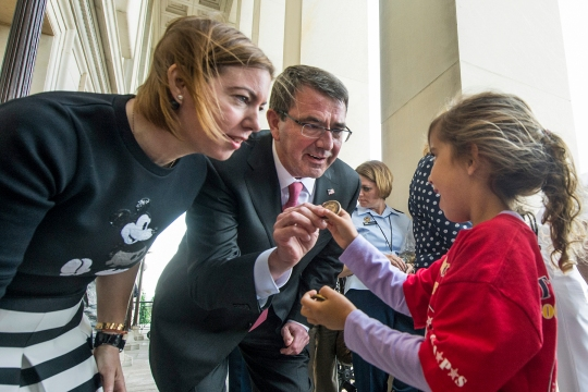 Secretary of Defense Ash Carter and his wife Stephanie present a coin to Layla Hornsby, daughter of the late Blackhawk helicopter pilot CW3 Brian Hornsby, at the Pentagon in Arlington, Va. May 22, 2015. The Carters welcomed Tragedy Assistance Program for Survivors family members to the Pentagon for an evening of events hosted by each of the services. (DoD News photo by EJ Hersom)