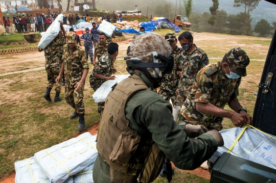 Nepalese service members gather relief aid delivered by a UH-1Y Huey helicopter with Joint Task Force 505 at an outlying village near Kathmandu, Nepal, May 7. The Nepalese government requested the U.S. government's assistance after a 7.8 magnitude earthquake struck the country, April 25. U.S. military services came together to form JTF 505, which works in conjunction with U.S. Agency for International Development and the international community, to provide unique capabilities to assist Nepal. (U.S. Marine Corps photo by MCIPAC Combat Camera Staff Sgt. Jeffrey D. Anderson)